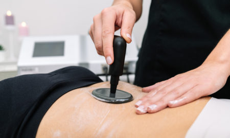 Short plane of Beautician giving radio frequency treatment to a woman in the stomach that outlines and stimulates healthy cell function, revitalization and cellulite removal